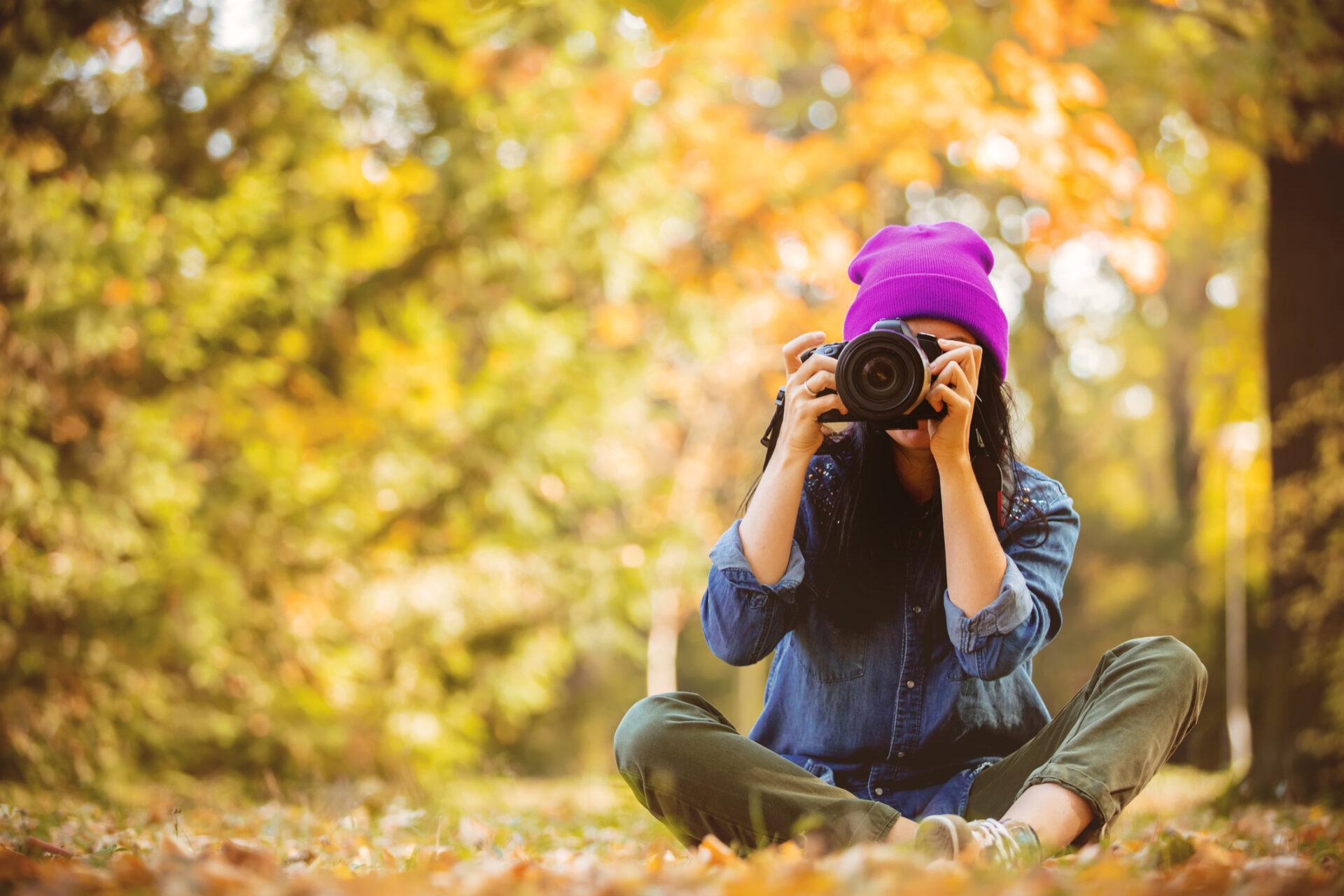 Frau sitzt im Wald am Boden und fotografiert